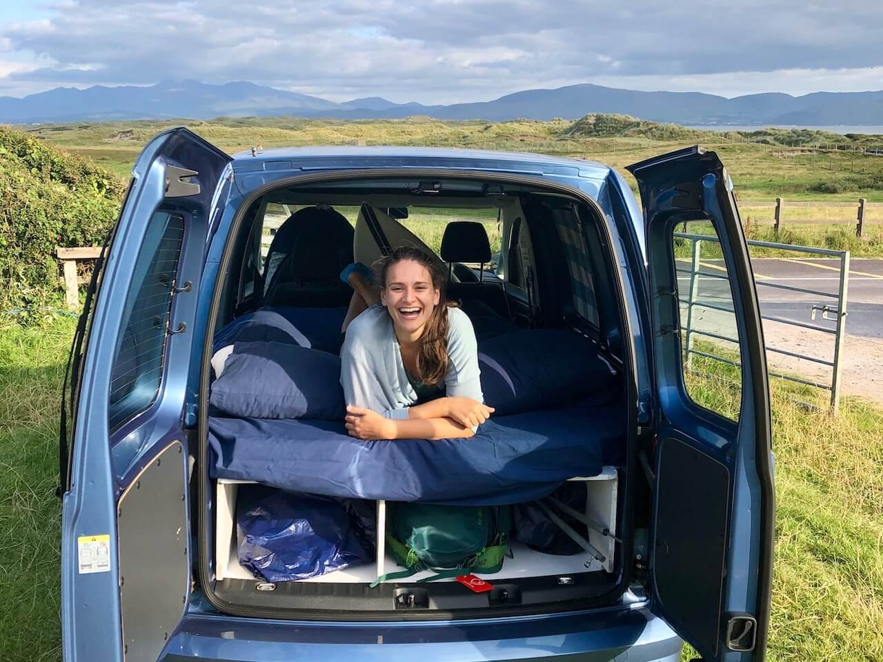 Nicola laying down on her stomach in a van with the back doors open. She's surrounded by fields and mountains and smiling at the camera.
