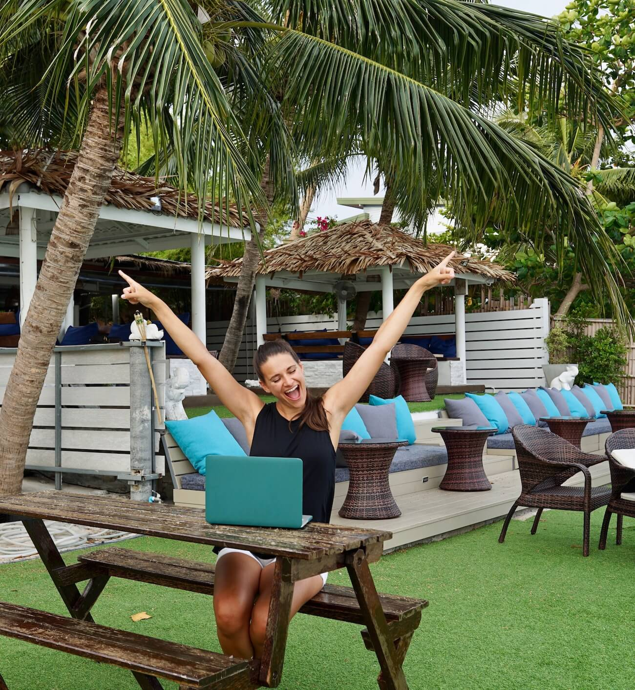 Nicola smiling with her arms spread wide and her two index fingers pointing up. She is working on her laptop with a palm tree and hotel in the background.