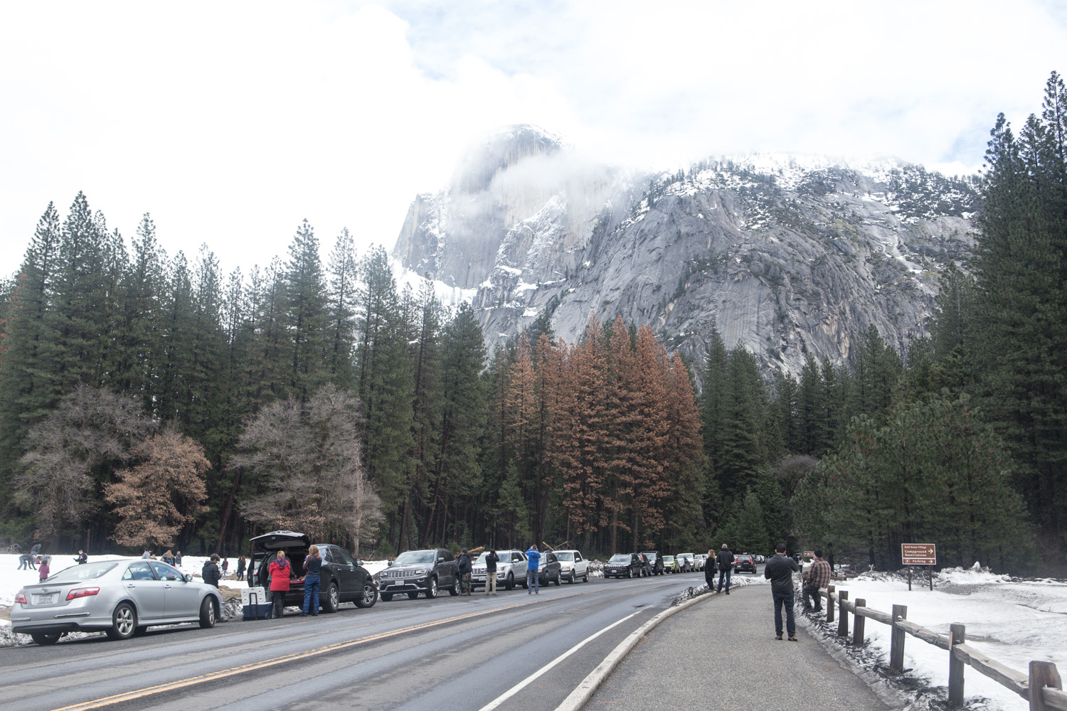 Road in Yosemite Valley in winter, with lots of people parked on the side of the road. Trees and a foggy view of a mountain are in the background.