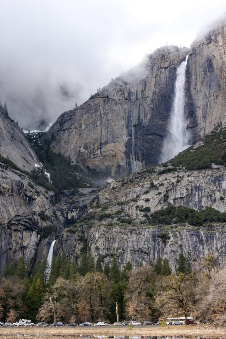 Upper and Lower Yosemite Falls with cars parked in front of them