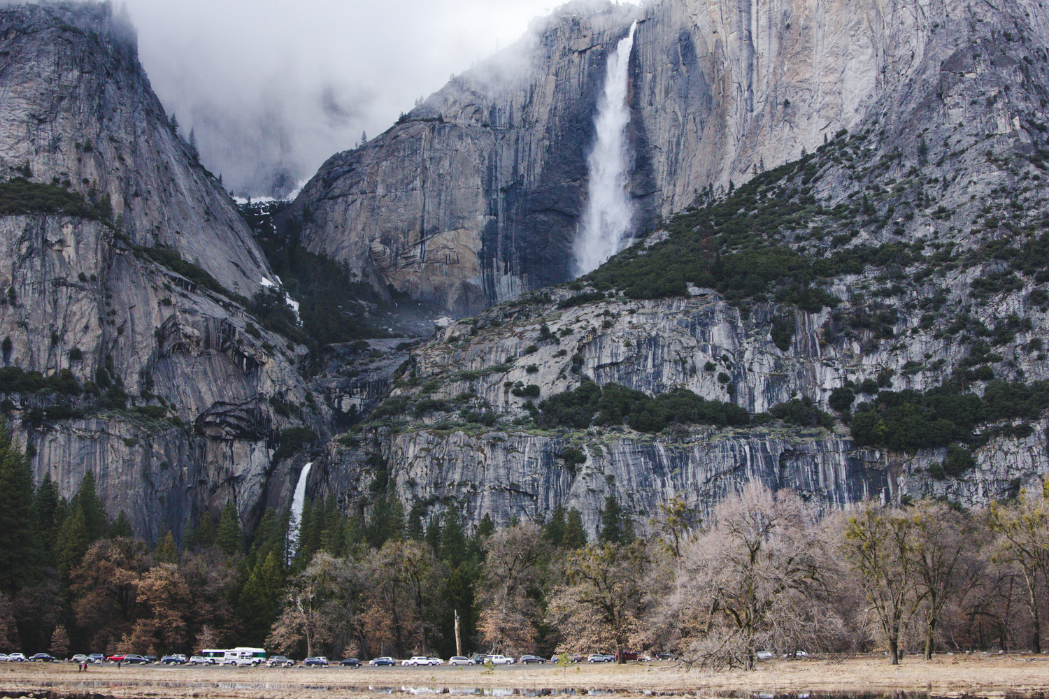 Upper & Lower Yosemite Falls surrounded by fog with cars parked along it