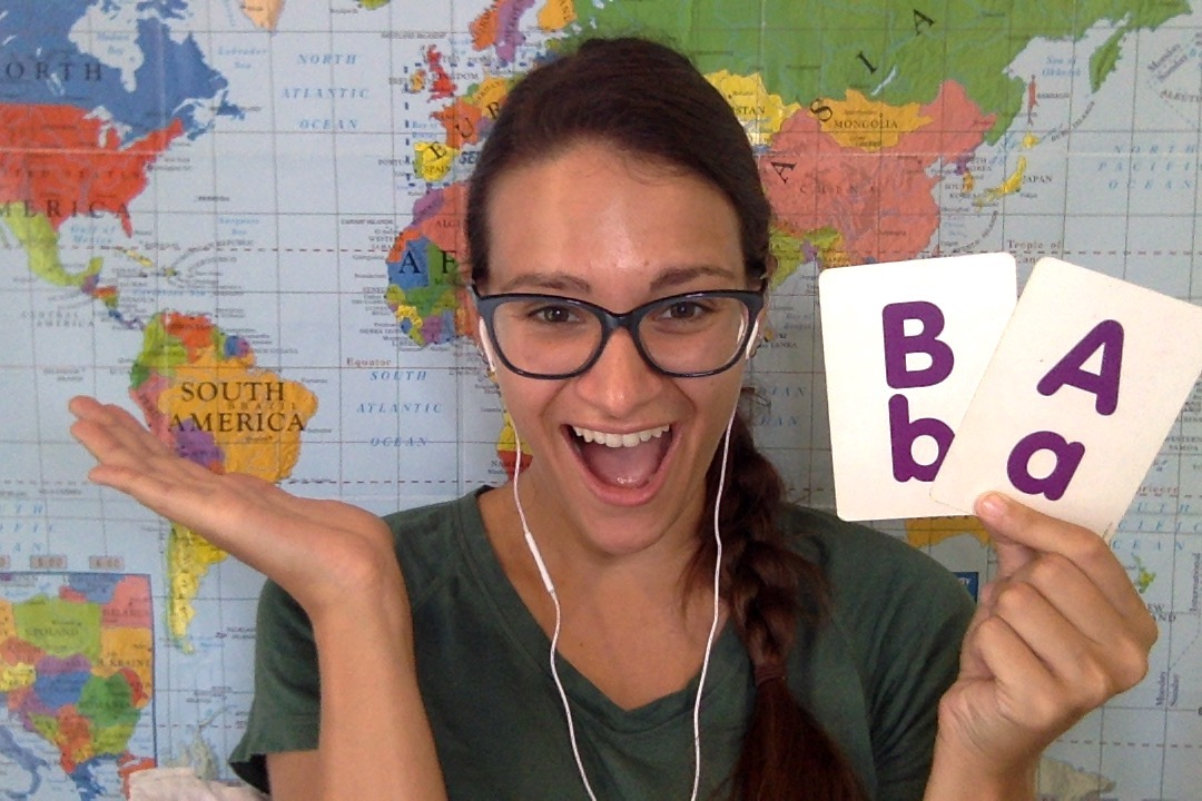 """Nicola, an online English teacher, holding 2 flashcards with """"Bb"""" and """"Aa"""" in front of a world map"""