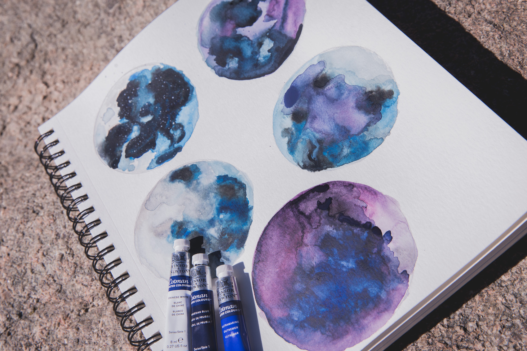 5 purple, blue, and black watercolor planets with 3 small paint tubes on the piece of watercolor paper