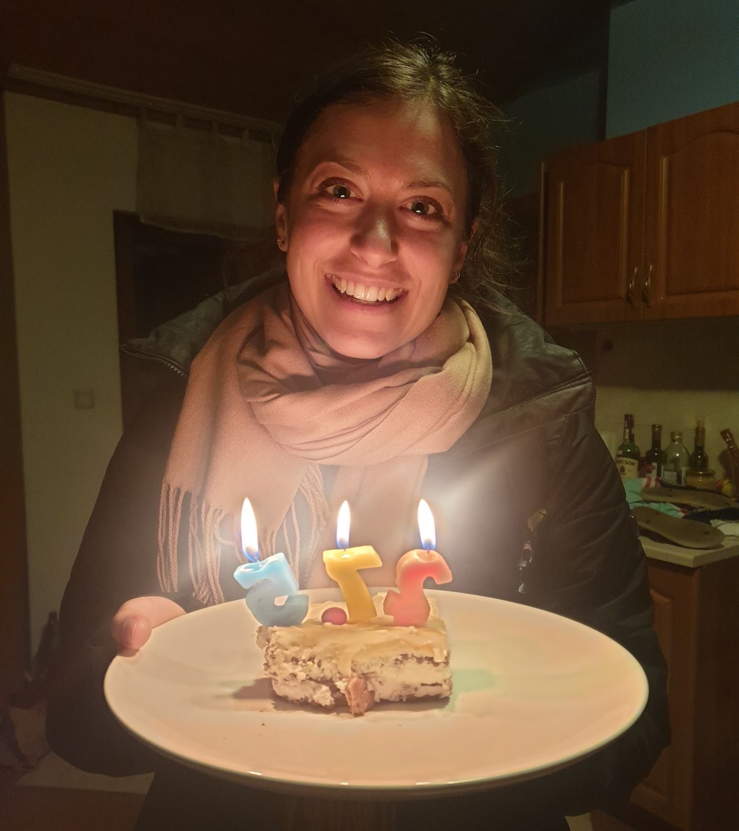 "Kelsey holding a plate with a slice of cake that has numbered candles that say ""27.5"". Kelsey is smiling and her face is lit by the candlelight."