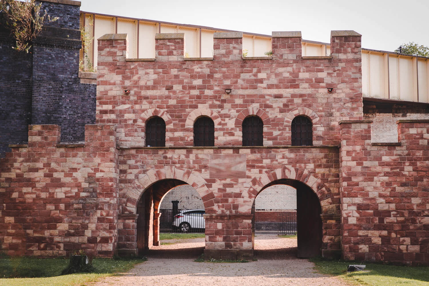 Ancient Roman City Gate to the fort of Mamucium in Manchester UK is made of red and cream bricks. There are 4 windows with two spots for cars to drive through.