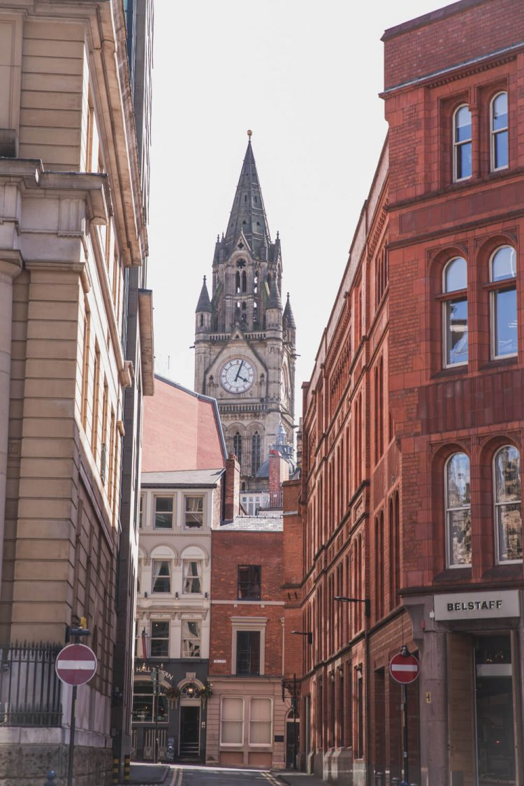 Buildings in Manchester made of red brick and the town hall in the background.
