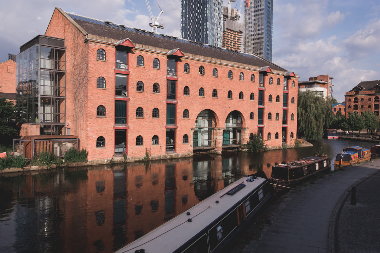 Brick building with many windows on a canal in Castlefield in Manchester, UK