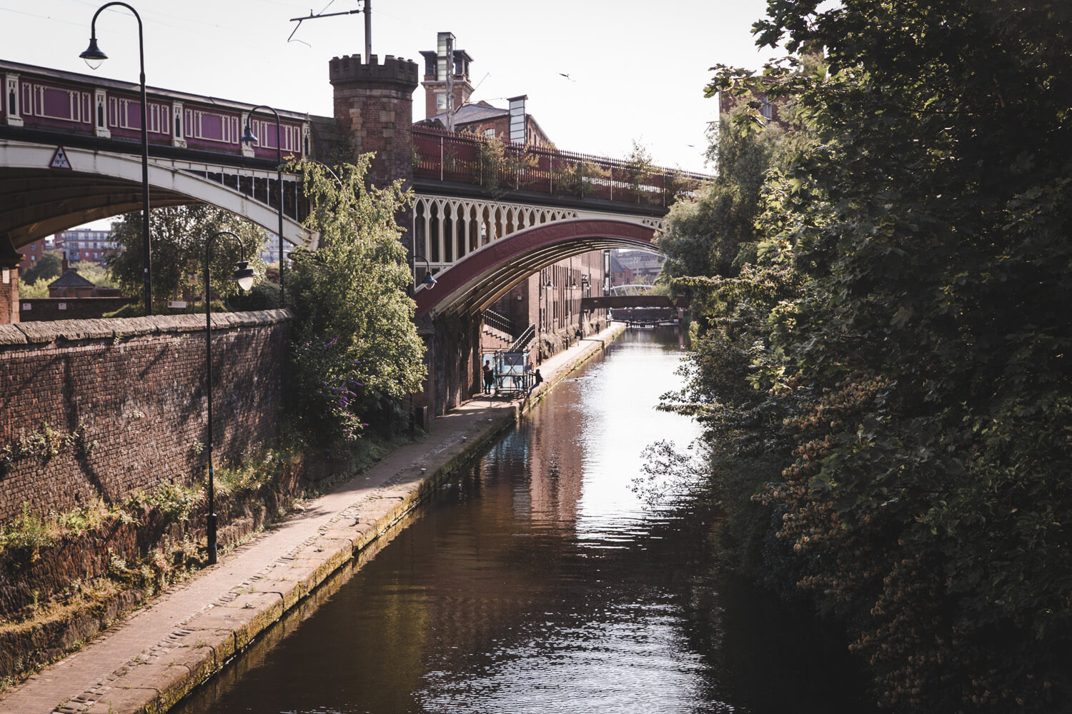 Canal in Manchester, UK with a bridge on top of it and trees growing next to it.