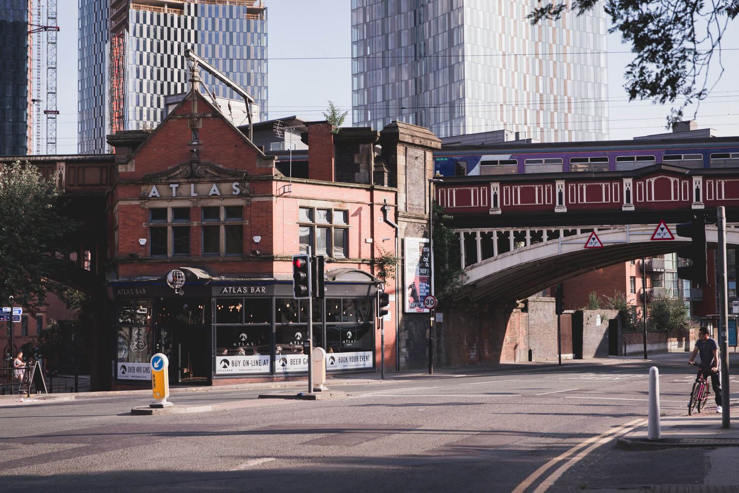 Castlefield Neighborhood buildings made of brick with a bridge in Manchester, UK. There are tall buildings in the background.
