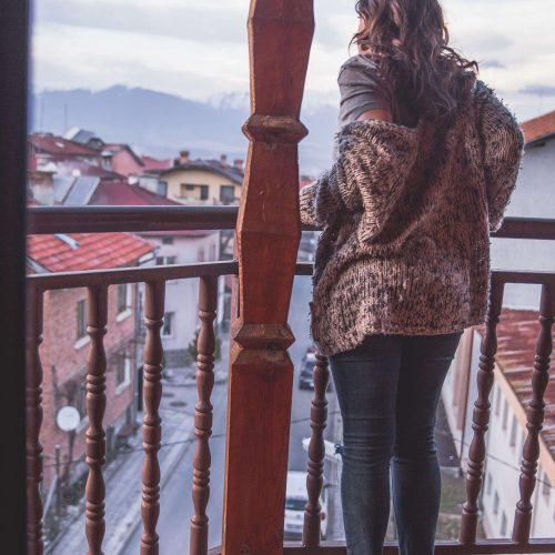 Kelsey standing on a balcony in Bansko, Bulgaria, looking out at the street, houses, and mountains in the distance.