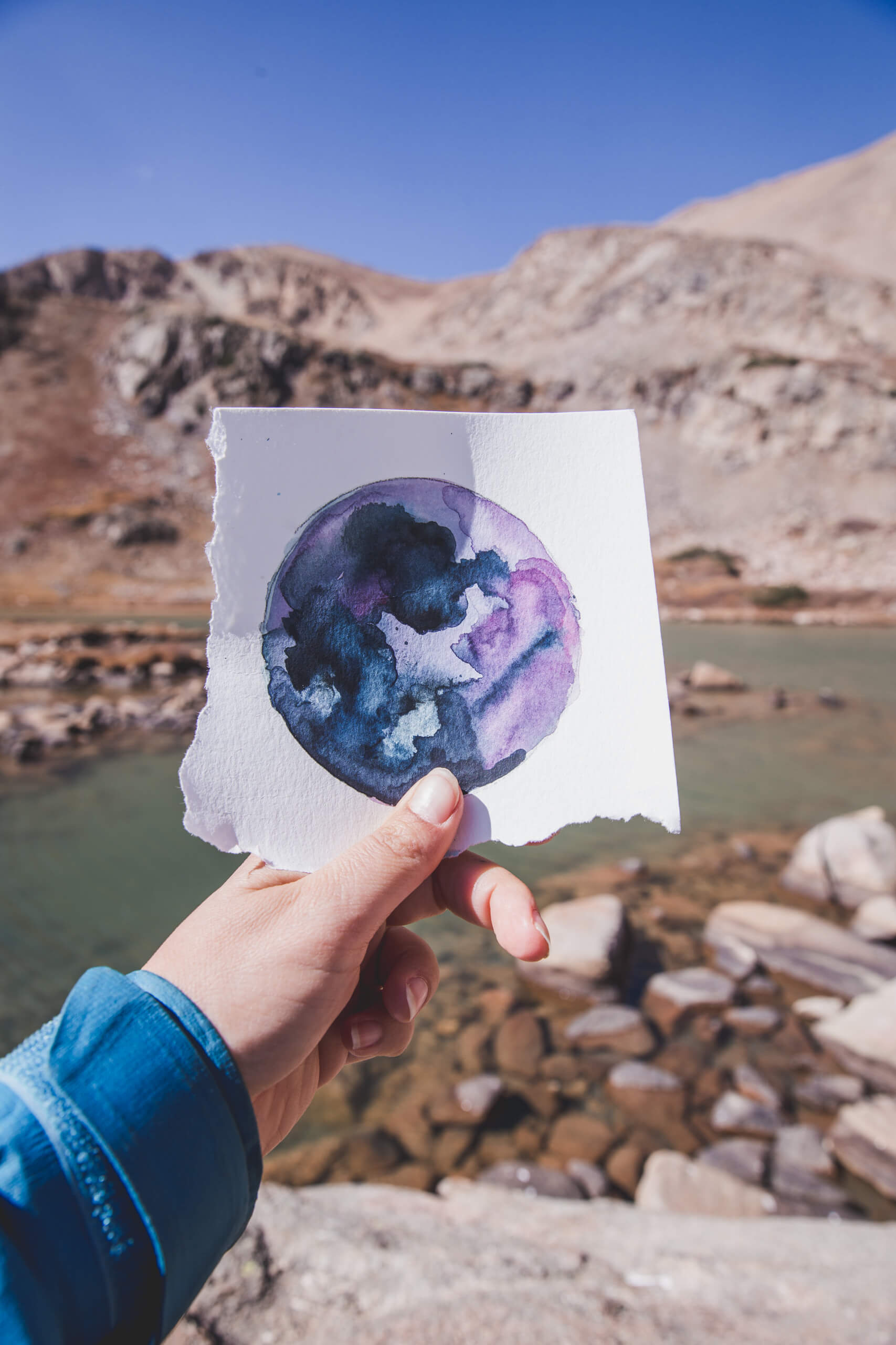 A hand holding a square watercolor planet painted with blue, purple, and black colors with a green lake and mountains in the background