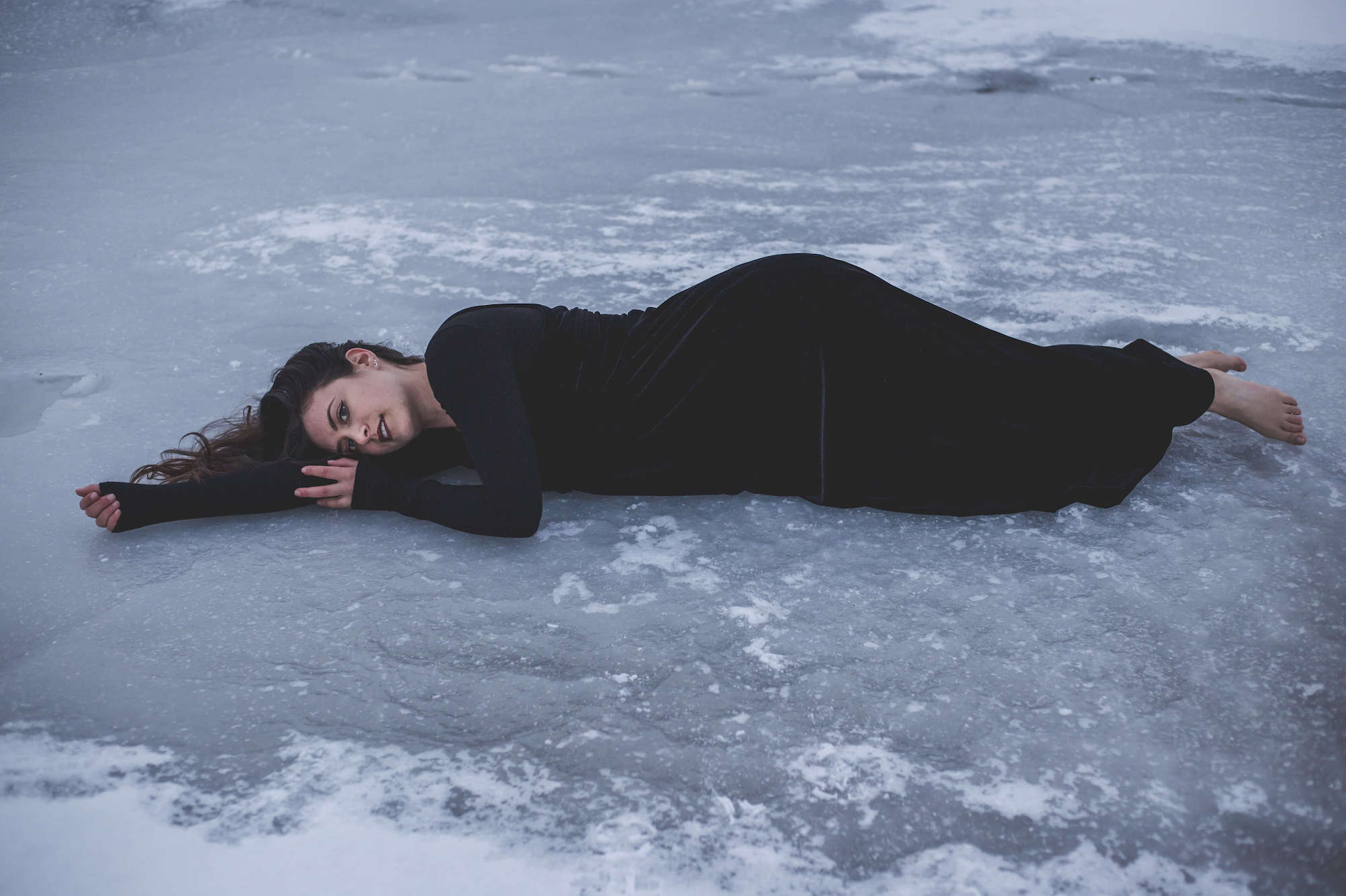 Kelsey laying on the ice in a black dress