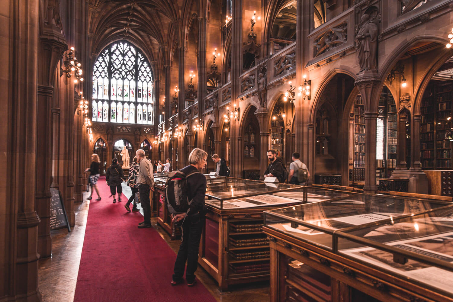 John Rylands Library in Manchester, UK has beautiful architecture with lights, desks, pretty windows, and a red carpet.