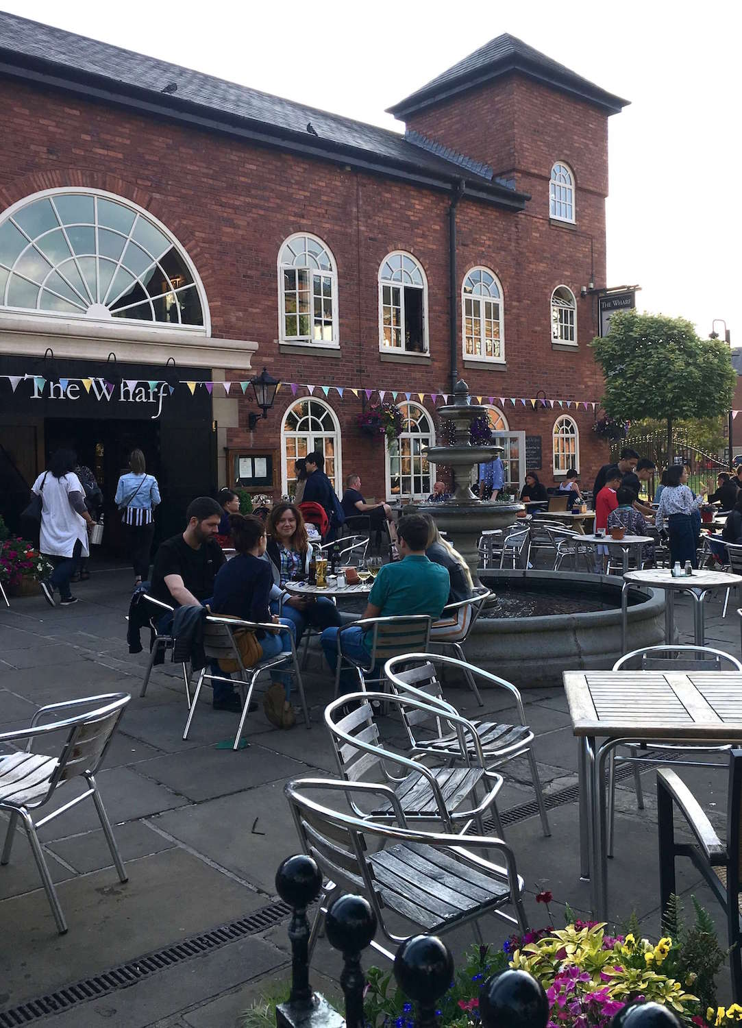 The Wharf is a brick restaurant in Manchester, UK with outdoor tables and chairs that people are sitting at.
