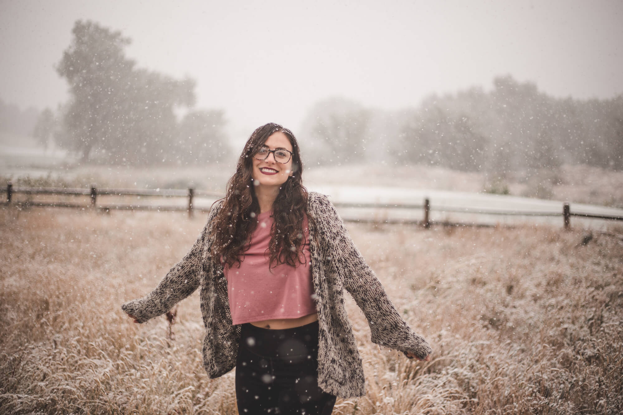 Kelsey is wearing glasses, a pink shirt, black and white cardigan, and smiling wide with her arms out during a snowfall in Colorado.