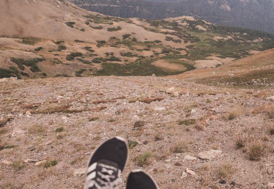 Shoes over Rocky Mountain National Park Lava Cliffs Overlook with mountains and a valley in view